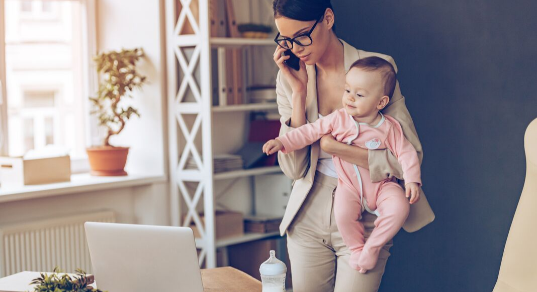 mom holding baby while working