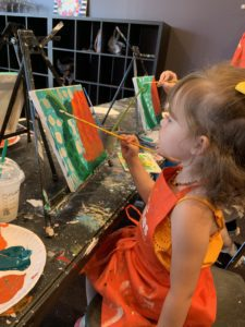 girl painting canvas at Pinot's Palette