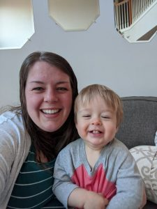 A woman sits on the couch, smiling with her toddler.