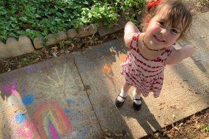 young girl displays sidewalk chalk art