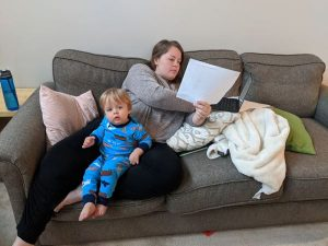 A woman is working on a couch while a toddler sits on her lap.