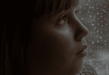 Child looking sad by rainy window