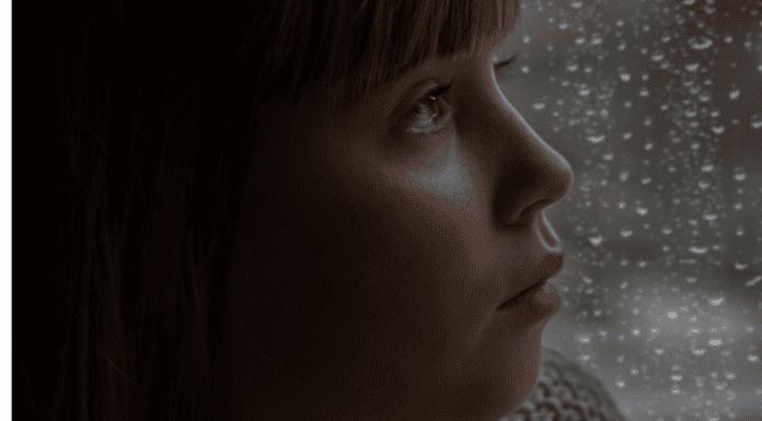 Child looking sad by rainy window
