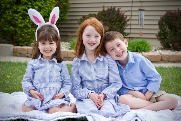 a pic of three smiling children in Easter outfits
