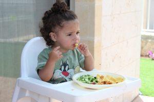 Little girl eating on her own