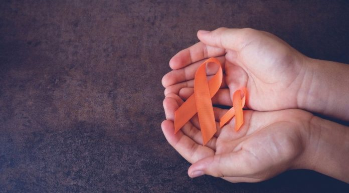 pic of hands holding orange ribbons for MS awareness
