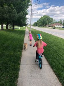 kids riding bike and walking dog