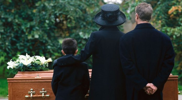pic of family standing by a casket