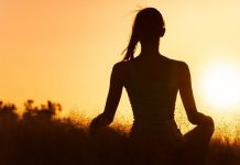 pic of a woman meditating at sunrise