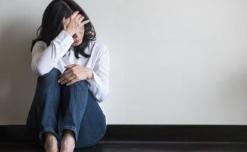pic of anxious woman holding her head, sitting on the floor