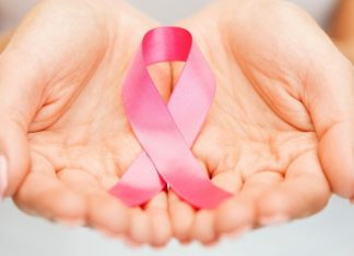 pic of woman's hands holding a pink ribbon