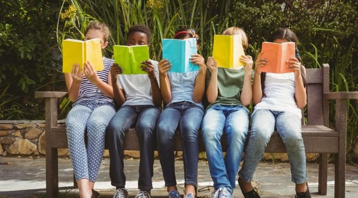 pic of five kids sitting on a bench reading books