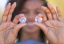"pic of woman holding up ""Vote 2020"" buttons"