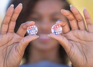 """pic of woman holding up """"Vote 2020"""" buttons"""