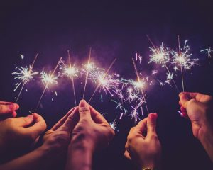 Hands holding lit sparklers to celebrate the new year