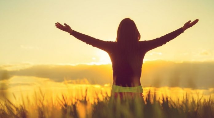 woman standing in a field at sunset, arms spread