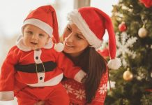 mother and baby both dressed for Christmas; baby wearing Santa outfit and Mom in Santa hat