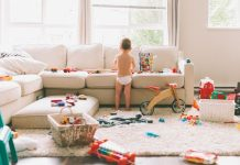 Messy living room, strewn with toys and a small child playing with them