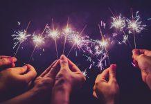multiple hands holding lit sparklers