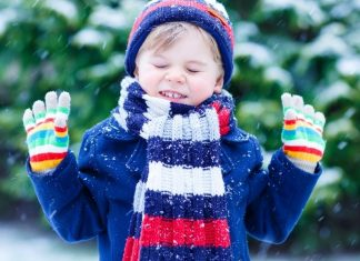 boy in winter layers outside in the snow