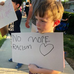 boy with no more racism sign