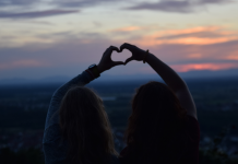 two friends making a heart with each of their hands outside at sunset