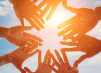 Eight open hands forming a circle in the sunlight
