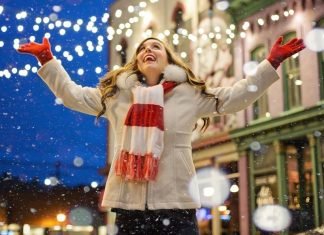 woman outside in winter enjoying holiday lights