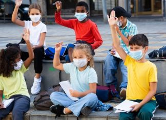 elementary-age kids wearing masks at school, raising hands to answer a question