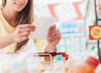 woman looking at a grocery list while at the store
