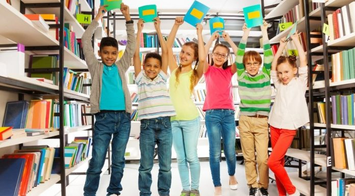 diverse group of kids in a library holding books