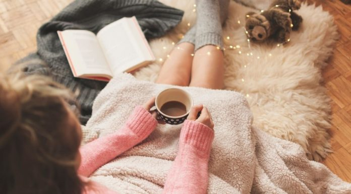 woman drinking hot cocoa, journaling, covered with a blanket