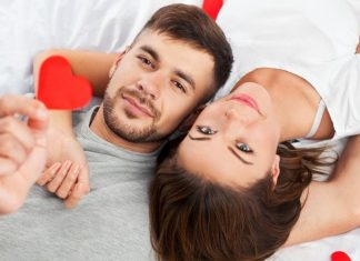 couple laying together holding hearts