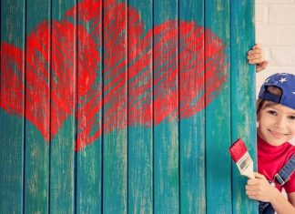kid paints red hearts on turquoise wall