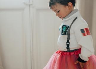 little boy wearing an astronaut costume and a pink tutu