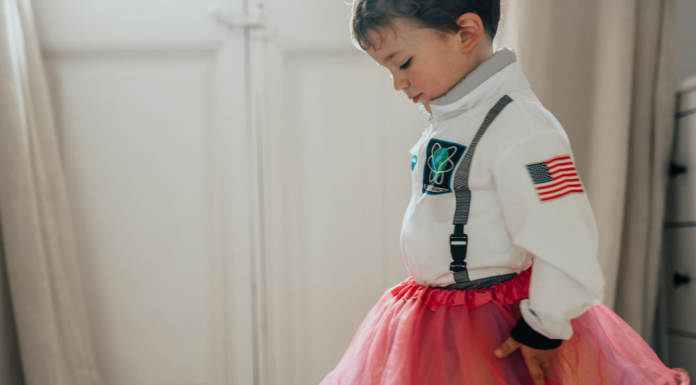 little boy wearing an astronaut costume and a pink tutu