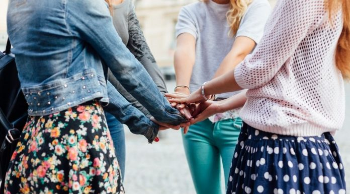 five girlfriends with hands in a circle