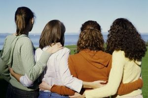 four girlfriends huddled together, arms around each other's backs