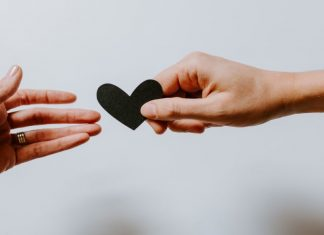 one hand giving another a heart