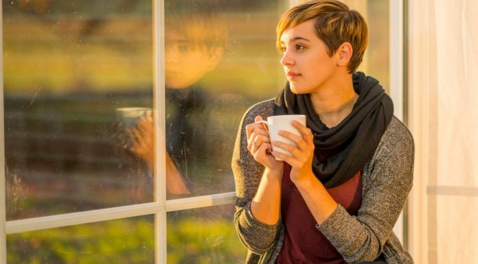 woman drinking coffee, looking out a window