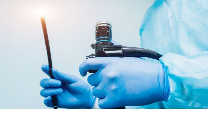 Doctor hands holding a scope and light used for colonoscopy