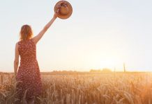 woman waving goodbye with a hat in a field at sunset