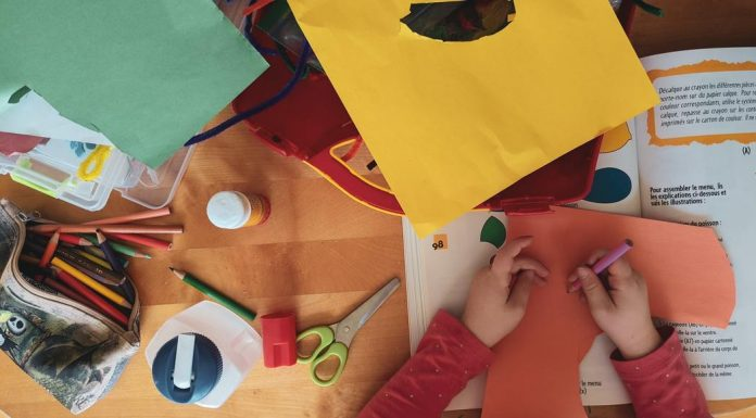 a child's hands doing craft with construction paper