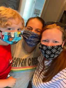 two moms and little boy wearing masks