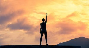 silhouette of woman on top of a mountain with her fist in the air