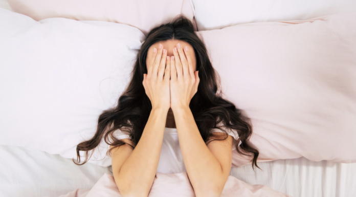 woman in bed with her hands on her face