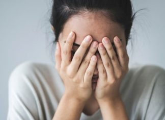 woman with her hands anxiously over her face