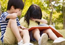 two asian children reading a book together
