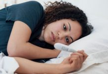 woman lying in bed, looking at a pregnancy test