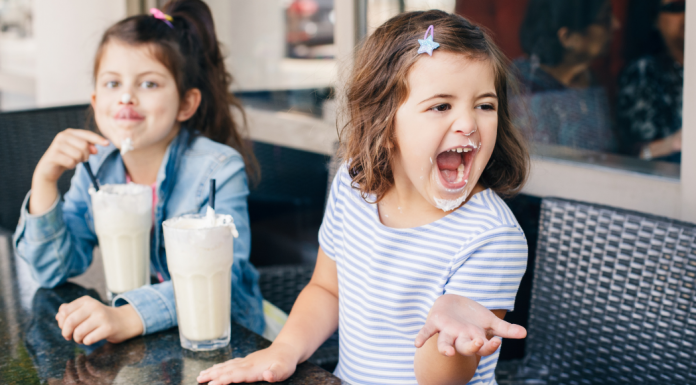 two girls drinking milkshakes on a restaurant patio